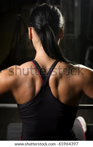 Asian woman working out on rower from behind - stock photo