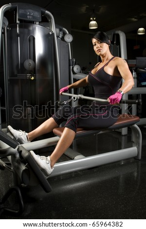 Asian woman working out on rower in gym - stock photo