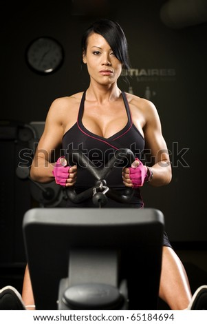 Asian woman working out on rower inside gym - stock photo