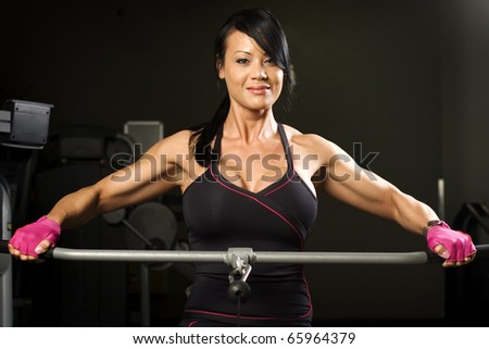 Asian woman working out on rower smiling - stock photo