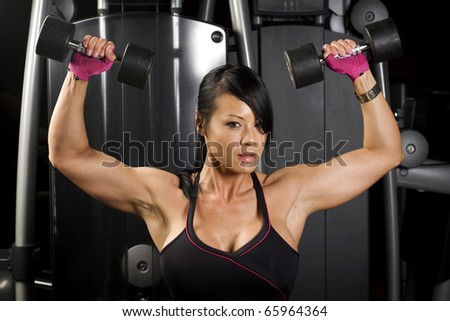 Asian woman working out with weights in gym - stock photo