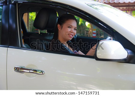 Asian women are driving white car. - stock photo