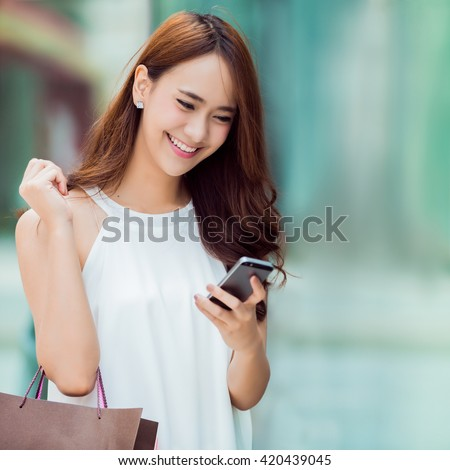 Asian women are shopping department store.she was on the phone to check stock - stock photo