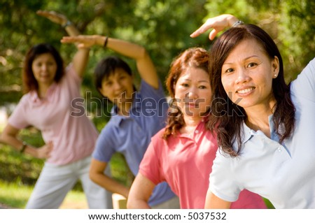 Asian women exercising in a park in the sunshine - stock photo