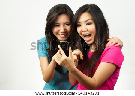 asian women having fun while texting with her phone - stock photo