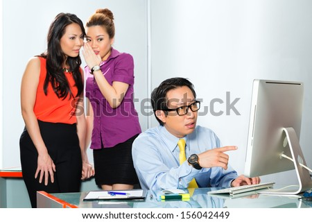 Asian Women or employee s tattle or whisper about colleague or man, bullying him in the office - stock photo