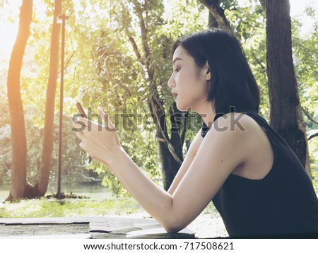 Asian women wear black jacket play a mobile phone at reservoir in morning.To shopping in social media.