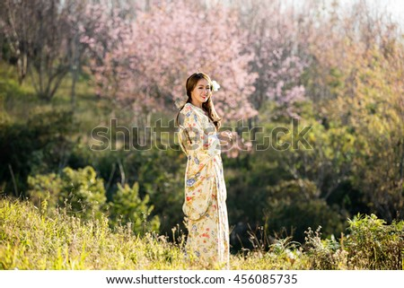 Asian women wearing traditional japanese kimono and red umbrella in the himalayan sakura garden,Thailand. - stock photo