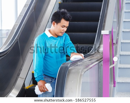 Asian worker cleaning escalators rubber handle use white color cloth - stock photo