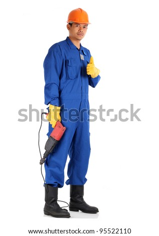 asian worker complete with personal protective equipment and electrical drill ready to work on safety concept - stock photo