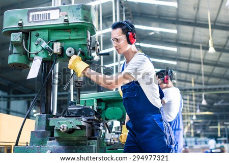 Asian worker in production plant drilling at machine on the factory floor - stock photo