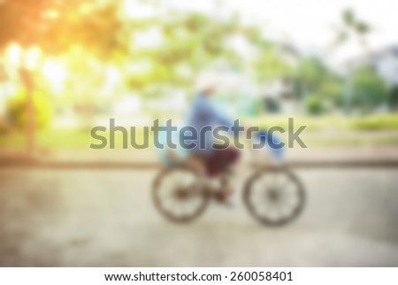 Asian worker riding a bicycle. High key blurred image with flare, bleached effect applied - stock photo