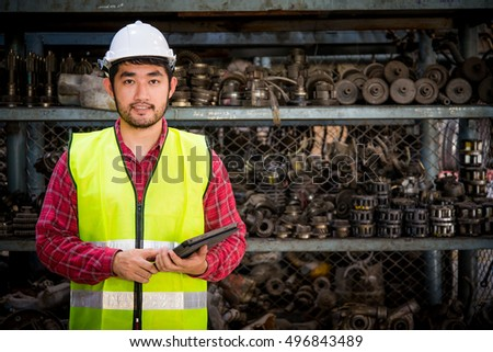 Asian worker with tablet on hands in factory warehouse car parts.