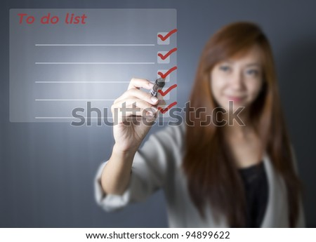 Asian working woman listing to do list.