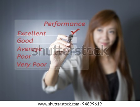 Asian working woman writing on performance audit checklist. - stock photo