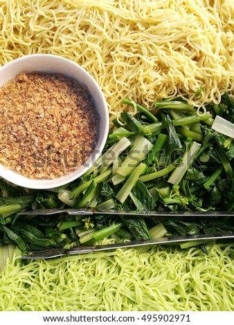 asian yellow noodles and green noodles with vegetable