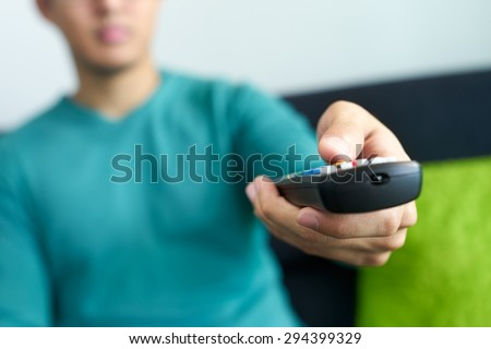 Asian young adult man watching TV and changing channel with remote control. Narrow focus on buttons and hand in foreground, cropped view. - stock photo