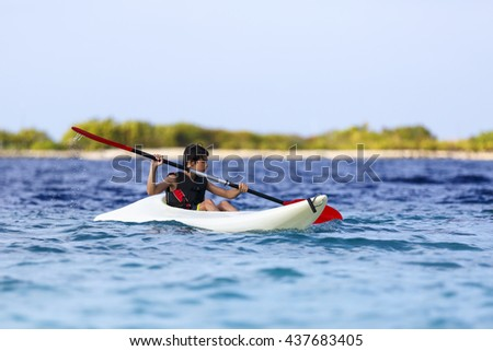 asian young boy rowing in sea kayak - stock photo