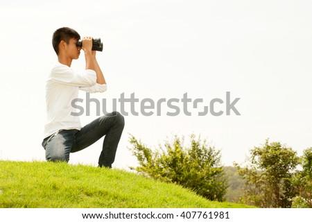 Asian young boy sit on mound seeking Binoculars . - stock photo