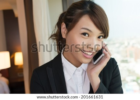 Asian young business woman using cellphone, closeup portrait in hotel. - stock photo