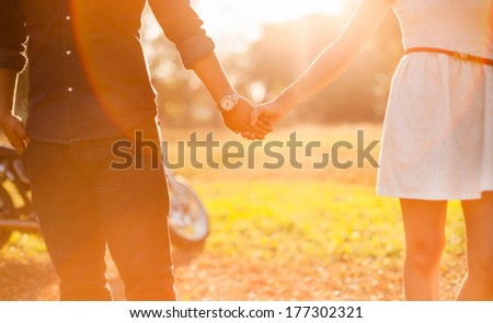 Asian Young couple in love walking in the autumn park holding hands  in the sunset - stock photo