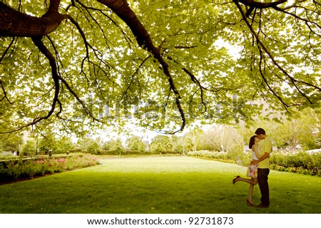 Asian young couple kissing under tree near St. Patrick Cathedral, Melbourne - Australia - stock photo