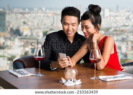 Asian young couple watching something on mobile phone - stock photo