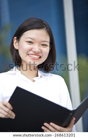 Asian young female executive holding a file