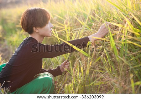 asian young female in the rice field in summer harvested field - stock photo