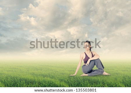 Asian young girl doing yoga exercise on grassland under dramatic cloudy sky. - stock photo