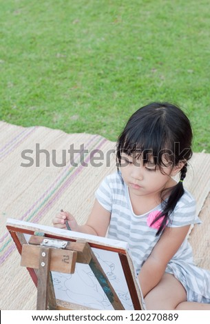 asian young girl painting in the park - stock photo