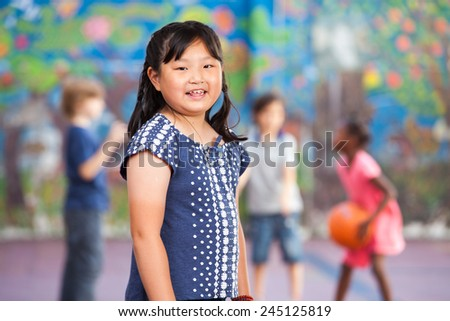 Asian young girl smiling in schoolyard while other kids playing basketball. - stock photo