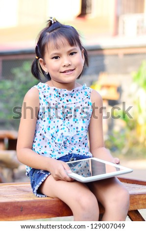 Asian young girl using computer tablet - stock photo