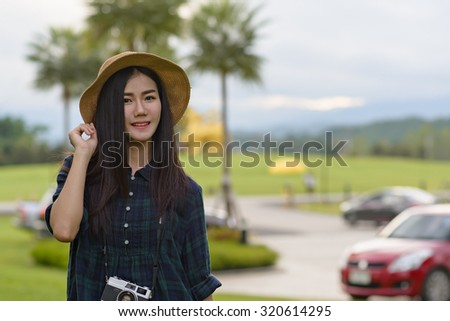 Asian young girl wearing straw hat with vintage camera walking o - stock photo