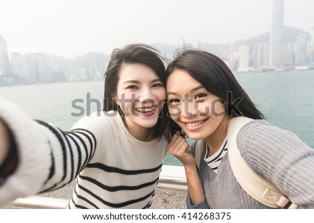 Asian young girls take a selfie with her friends at Victoria Harbor, Hong Kong. - stock photo