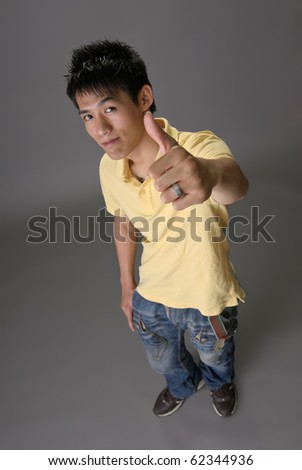Asian young guy give you excellent sin over studio gray background. - stock photo