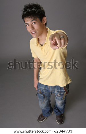 Asian young guy point at you over studio gray background. - stock photo