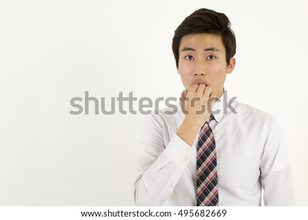 Asian young handsome man scared and afraid with fingers in mouth