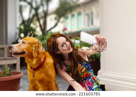 Asian young lady taking a selfie with her dog at the patio - stock photo