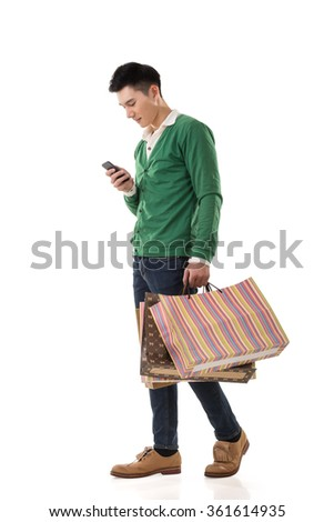 Asian young man holding shopping bags and using cellphone, full length portrait isolated. - stock photo