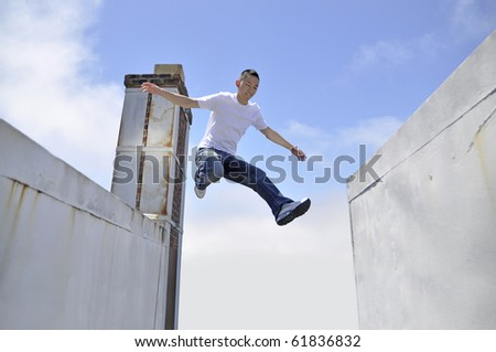 Asian young man making a giant leap in between buildings - stock photo