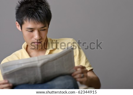 Asian young man reading newspaper over studio gray background. - stock photo