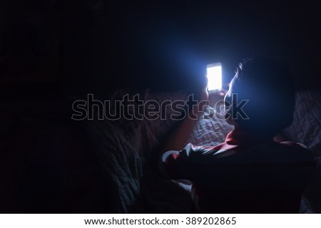 Asian young man using his mobile phone on the bed in dark room. Thin guy playing his smartphone on the bed in dark room. - stock photo