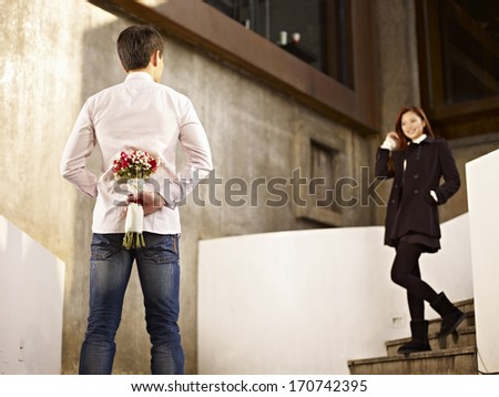 asian young man waiting by the steps with flowers behind back for his girlfriend. - stock photo