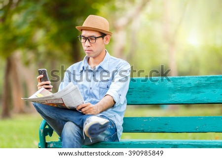Asian young Man with hat sitting on a wooden bench and reading a newspaper and checking message by smartphone screen with a serious expression in a park - stock photo