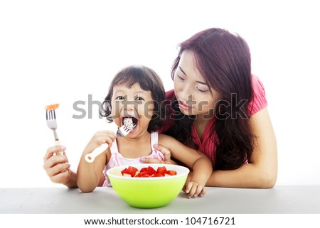 Asian young mother helping her daughter eats fruit salad