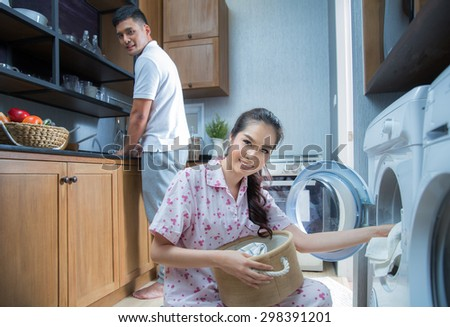Asian young wife putting a cloth into washing machine with her husband - stock photo