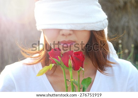 Asian young woman are bind with white scarf on her eyes in the light and flare in sunshine evening. In concept love is blind. - stock photo