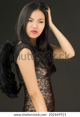 Asian young woman dressed up as a black angel scratching her head - stock photo