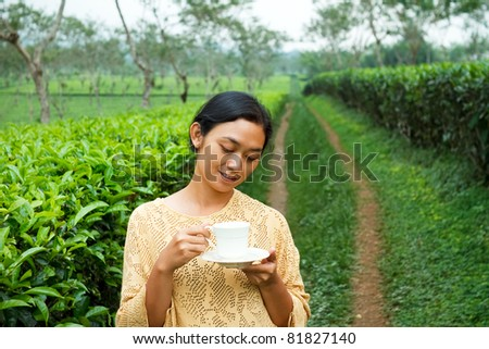 Asian young woman drink a cup of healthy tea at tea plantation - stock photo
